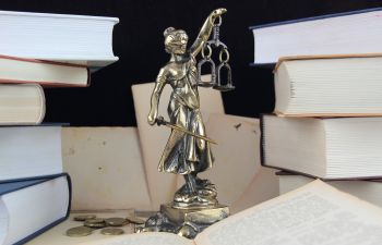 justice statue surrounded by piles of books