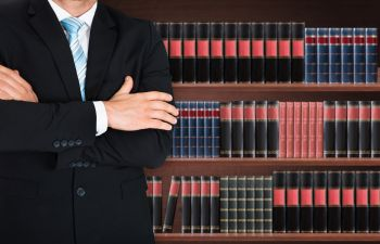 a man with folded arms with lawyer's library in the background