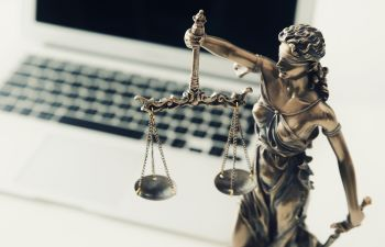 justice scales next to laptop