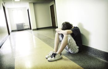 a teenager with head hidden in his arms sitting by the wall of a hallway