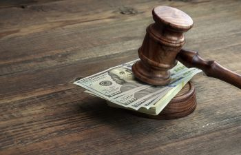 judge's gavel leaning on dollar banknotes