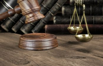 judge's gavel and justice scales with books in the background