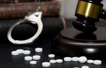 pills and judge's gavel with handcuffs and books in the background