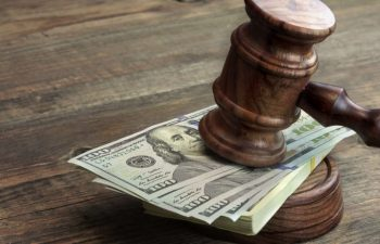 judge's gavel leaning on pile of American dollars